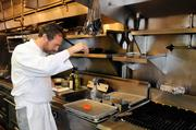 At Biba Restaurant in Sacramento, chef Steve Toso seasons a piece of salmon.