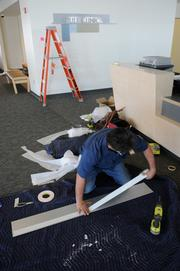 A worker from Ellis & Ellis Sign Co. installs a sign in the new wing of the UC Davis Comprehensive Cancer Center, before it opened to patients.