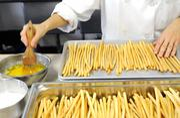 In the kitchen of Biba Restaurant in Sacramento, Penny Sheridan-Rimmele spreads butter on bread sticks.