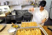 Penny Sheridan-Rimmele, an assistant pastry chef and baker at Biba Restaurant in Sacramento, seasons bread sticks.
