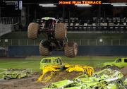 A monster truck leaps a junked vehicle. Organizers brought 70 junked cars and two buses for monster mayhem. Some of the junked vehicles were painted in a bright electric lime green color.