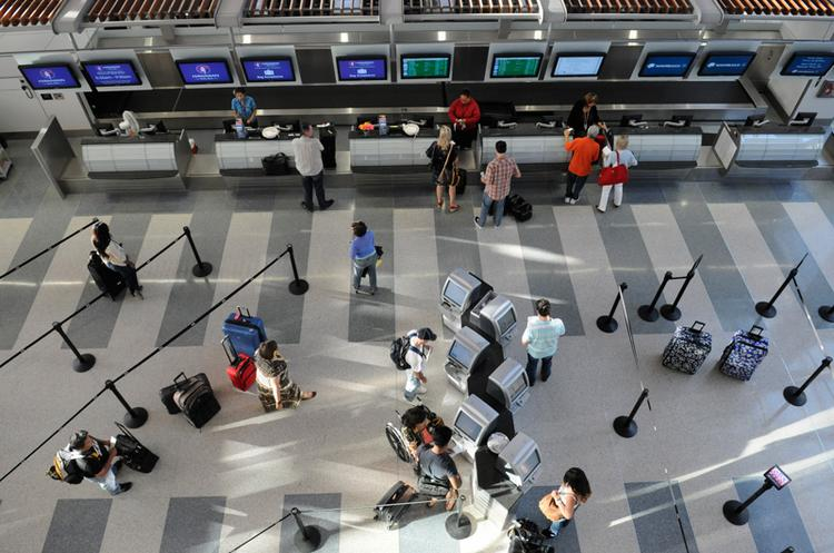 """A year after the $1.03 billion """"Big Build"""" project opened to the public, the Sacramento County Airport System is aggressively looking at ways to boost revenue and reduce costs to help make Sacramento International Airport more competitive. With declines in passenger traffic, that's becoming harder to achieve.    The goal was to photograph passengers checking in for their flights. I started on the second level, but I wasn't satisfied with the images I was getting, so I moved to the third level. The light and angle were both more interesting from higher above.  From the story: Airport looks to hike revenue as passenger volume drops"""