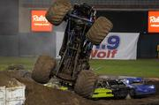 A monster truck crushes its way over some vehicles and dirt at Raley Field. The monster effort to change a baseball field into a monster truck rally took more than 2,500 yards of dirt, with 70 junk cars and two buses.