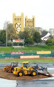 A work crew begins spreading dirt to create a monster truck track at Raley Field. It took days to transform the field into a monster truck track.