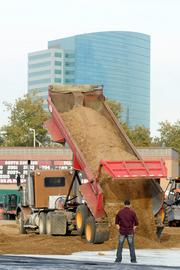 A truck dumps a load of dirt on top of a protective sheet of plastic at Raley Field. It took 166 trips with 20 trucks to transform the baseball field into a monster truck track.