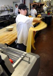 Penny Sheridan-Rimmele, a baker at Biba in Sacramento, finishes pulling pasta for fettucine out of machine.
