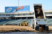 A truck dumps a load of dirt. It took 166 trips to prepare the baseball field for a monster truck rally.