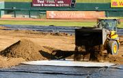 A worker spreads dirt over protective plastic at Raley Field in preparation for a monster truck rally. To go from green to monster mean, it took 2,500 yards of dirt.