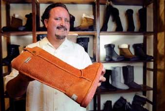 Tom Romeo displays one of his Bearpaw brand boots at his Citrus Heights display room. Bearpaw Footwear has hired logistics company Kuehne + Nagel to provide international transportation and U.S. distribution.