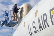 "Dan Gutierrez stands on a lift to remove flaking paint from the ""radome"" of a Lockheed EC-121D ""Warning Star"" at the Aerospace Museum of California. The dome protects electromagnetic detection gear inside the aircraft, which provided early warning of enemy aircraft during the Vietnam War."
