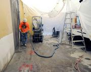 Terry Estes of Johnson's Concrete Sawing vacuums slurry created when workers cut a new doorway at Cafe Bernardo. The dining area is still under construction.