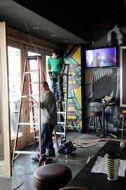 Workers Eric Johnson and Alex Tyler of Capital Painting and Construction install molding above the door.
