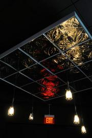A view of lights and a tin ceiling highlights the visual interest in the space.