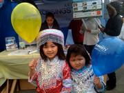 Girls stand in front of a Crossings TV booth at a Hmong New Year celebration. Crossings TV produces its own news and entertainment programming, including covering other local events such as the Chinese New Year parade and the Yuba City Marysville Sikh Festival.