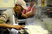 A member of the kitchen staff fluffs steamed rice in the kitchen of Frank Fat's restaurant in downtown Sacramento.