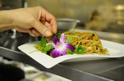 A cook garnishes Sang Gai Shee Chow Mein in the kitchen of Frank Fat's restaurant in downtown Sacramento.