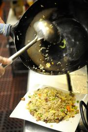 A cook transfers barbecued pork fried rice to a plate at Frank Fat's restaurant in downtown Sacramento.