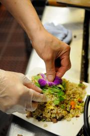 A cook garnishes barbecued pork fried rice -- a signature dish at Frank Fat's restaurant in downtown Sacramento.