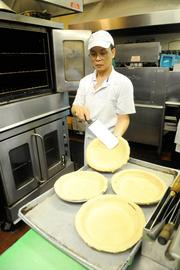 Kitchen staff pull pie shells from an oven in the kitchen of Frank Fat's restaurant in downtown Sacramento. Banana creme and chocolate creme pies are signature dishes at the restaurant.
