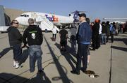 People wait to board the retired Boeing 727-200F after landing at McClellan Business Park.  FedEx donated the aircraft to support aeronautic and aviation training.