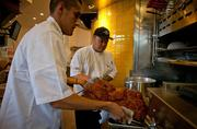 Chef Christian Palmos, right, oversees the smoking of some pork at Firestone Public House. The menu is said to be an eclectic mix of American cuisine and comfort food, with items prepared in a demonstration kitchen as well as from a wood-fired pizza oven and a barbecue smoker.