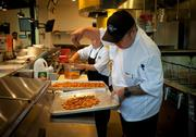 Chef Christian Palmos and staff practice preparing dishes. The menu is said to be an eclectic mix of American cuisine and comfort food, with items prepared in a demonstration kitchen as well as from a wood-fired pizza oven and a barbecue smoker.