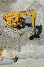 Rock is excavated during construction of an auxiliary spillway at Folsom Dam.