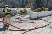 A worker at the auxiliary dam project sprays a surface down with water.