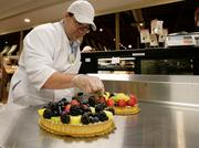 Bakery coordinator Mike Westbrook assembles fresh fruit tarts. The Fresh Market's ovens are busy from 5 a.m. to 5 p.m. and the bakery is open until 9 p.m.