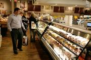 Shoppers eye the selection at the deli and rotisserie section at The Fresh Market.
