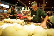 The Fresh Market trainer Jim Ford sets out freshly cut melon slices.