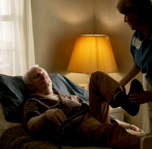 Older man receiving at-home care in a bed