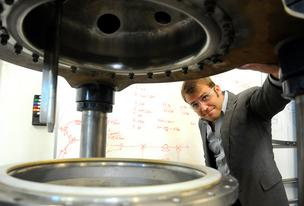 Micromidas CEO John Bissell looks into a reactor that digests cellulose. Micromidas plans to convert cellulosic waste material into paraxylene, which is used to make plastics