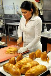Erika Ramirez slices sourdough bread to be served at a seating at The Kitchen.