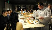 Mike Ward plates sweetbreads at a seating of The Kitchen while guests Naveed Sufi and Citra Mulia watch.
