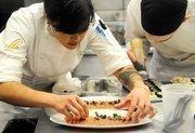 Leslie Peng and Joshua Thomas prepare cured salmon at a seating at The Kitchen.