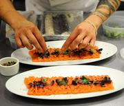 Leslie Peng puts the final touches on cured salmon before serving at The Kitchen.