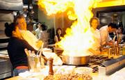 Part of the experience at The Kitchen is audience participation. Executive chef Randall Selland chooses guest Samme Mao to help with the flambe.