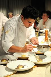 Paul Di Perro puts mushrooms on au gratin potatoes at The Kitchen.