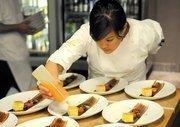 Leslie Peng puts blood orange glaze on dessert before serving at The Kitchen.