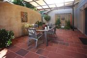 Luciole Design transformed a two-level deck into an elegant, tiled patio under a metal-and-shade-cloth structure.