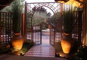 This Moroccan style gate opens on to a fountain courtyard surrounded by climbing roses.