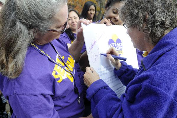 "SEIU-UHW started contract negotiations Tuesday on behalf of thousands of workers at Catholic Healthcare West. SEIU-UHW member Cathi Cline, also a 37-year-employee of Mercy General Hospital, signs the union's ""Let's Get Healthy California"" pledge at a rally on Thursday. The union said it wants to focus on improving quality of care."
