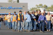 San Francisco-based PG&E plans to send more than 150 employees to help restore power in New York. The first group of workers from Northern and Central California walk to a charter aircraft at Mather Airport to begin their journey.