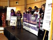 Some Sacramento Kings fans stand on mini stage for photos before the mayor's news conference begins.