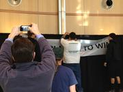 "Sacramento Kings fans take pictures of a sign proclaiming ""Playing to win."""