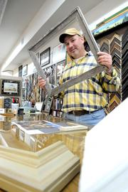 """Business owners in downtown Lincoln are eagerly awaiting next month's opening of the Highway 65 Lincoln bypass, which they say will relieve traffic backups and encourage locals to park and walk in the city's historic downtown.     Sierra Hills Framing owner Tom Jones is one of those business owners looking forward to seeing a change downtown. """"With less traffic and big vehicles, more people that live in Lincoln will feel more comfortable coming down,"""" he said.      There are many images out there with someone looking through a picture frame, but I wanted to produce an image that didn't seem contrived. I liked how the converging lines started in the upper right corner and directs you to Jones, and then toward the back of the store. Even the silver frame corner adds to the converging lines.   From the story: Lincoln's downtown shop owners hope bypass will give them a boost"""