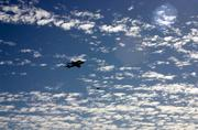 The shuttle Endeavour passes over Sacramento, as seen from atop a downtown parking garage.