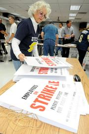 "Beatrice ""Bea"" Medinas with United Food and Commercial Workers Local 8 prepares for a possible strike by attaching strike signs to sticks."