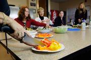 A salad potluck lunch at Pacific Coast Builders is a big hit with, from left, Martha Fierro (holding knife), Sandra Forrest, Jeanne Wilson, Karisa Stahle and Elise Faulkner-Glantz.